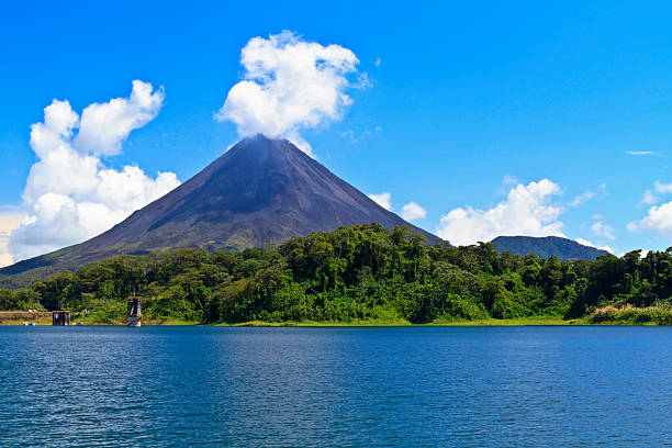 Arenal Volcano and Lake Arenal Volcano 'puffs' out a cloud above the rainforest on the shores of Lake Arenal in Costa Rica volcano stock pictures, royalty-free photos & images