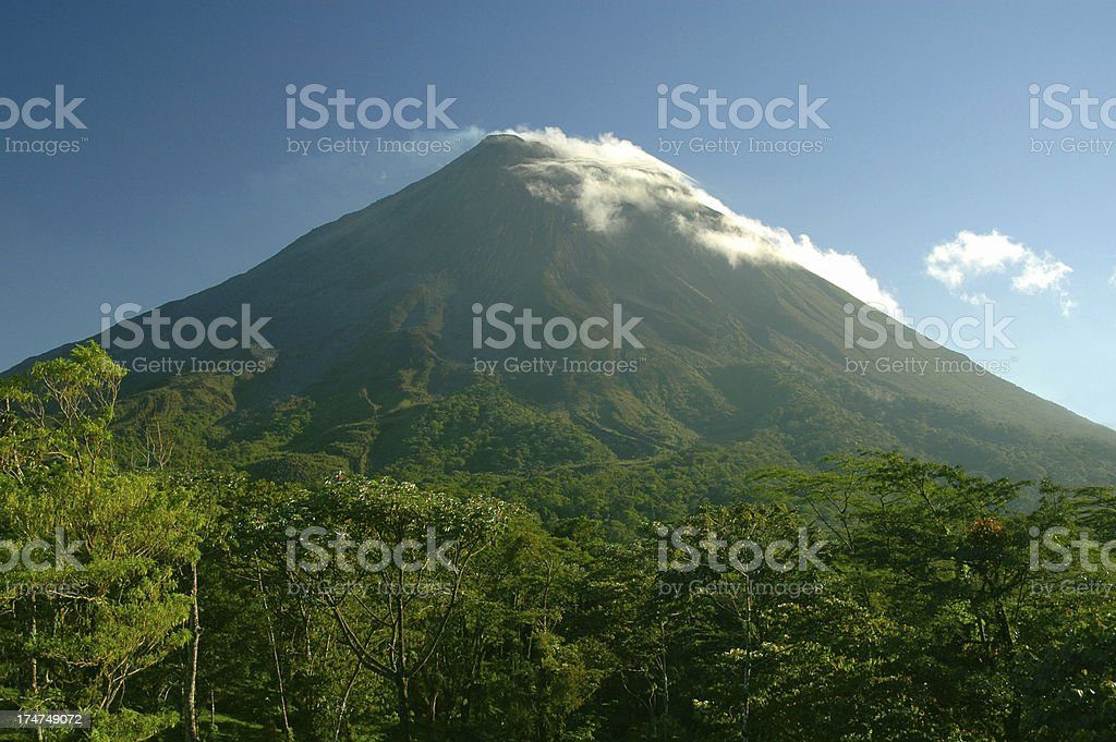 Arenal volcano Costa Rica. Cloud capped cone against blue sky. royalty-free stock photo