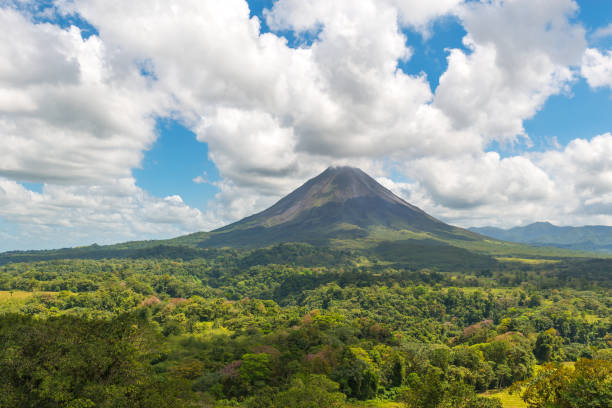 Arenal Volcano in Costa Rica The majestic Arenal volcano surrounded by tropical rainforest on a warm summer day near La Fortuna, Costa Rica, Central America. limoen stock pictures, royalty-free photos & images