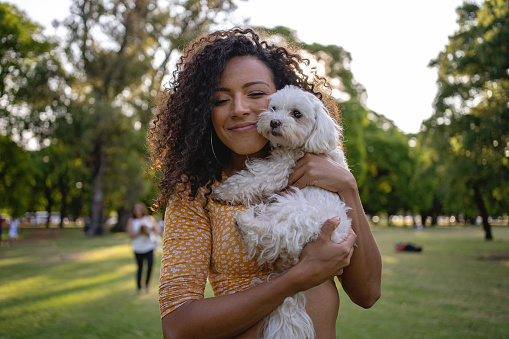 Carefree young woman, relaxing at public park in Buenos Aires while holding her dog bichon frise