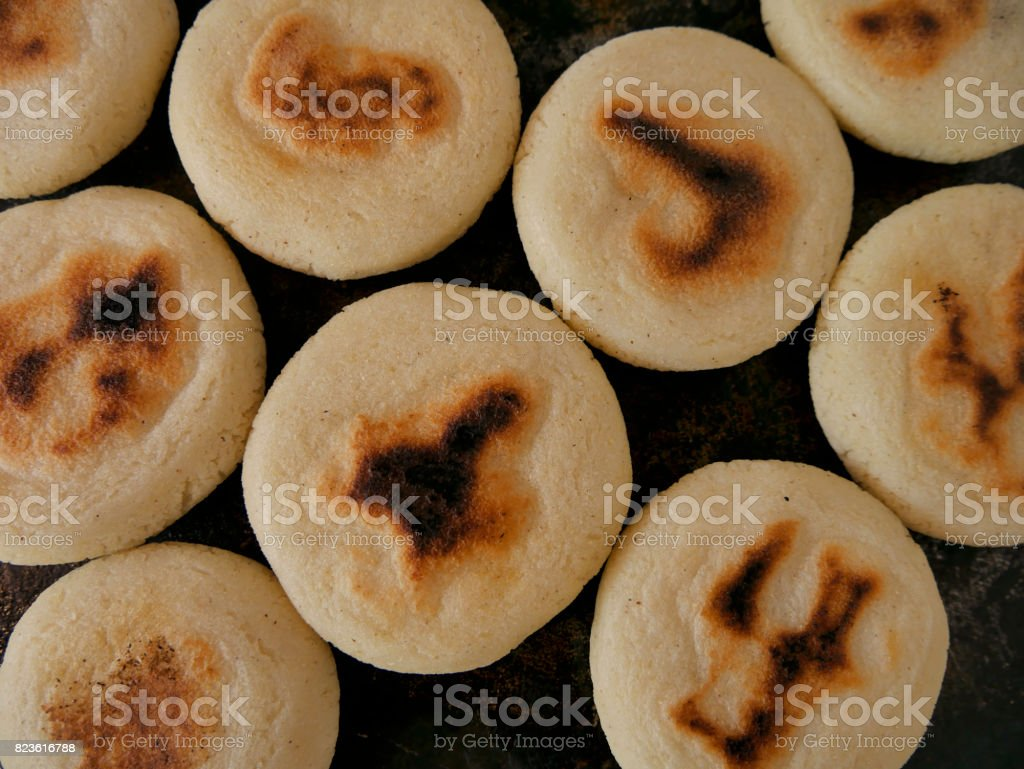 Arepas cooking on grill stock photo