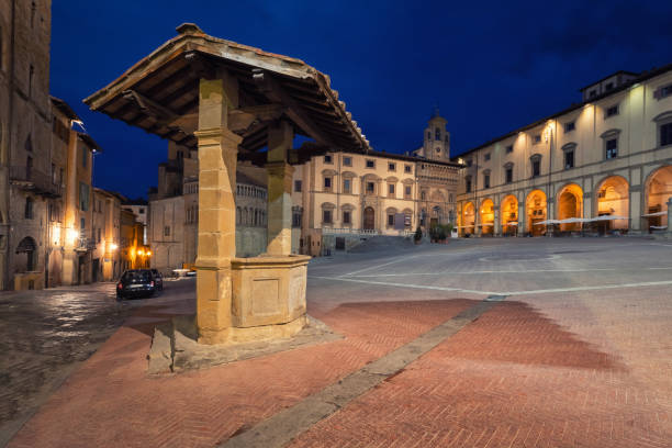 Arezzo, Italy. Piazza Grande and old well Arezzo, Italy. Old well located on Piazza Grande square at dusk arezzo stock pictures, royalty-free photos & images