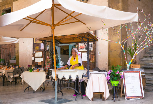 Arezzo, Tuscany, Italy,  Chef preparing a Pizza outside Arezzo, Tuscany, Italy May 21, 2018: A chef preparing a Pizza outside the restaurant in Arezzo Old-town arezzo stock pictures, royalty-free photos & images