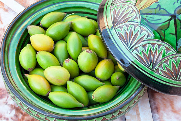 Argan nuts in a green plate. stock photo