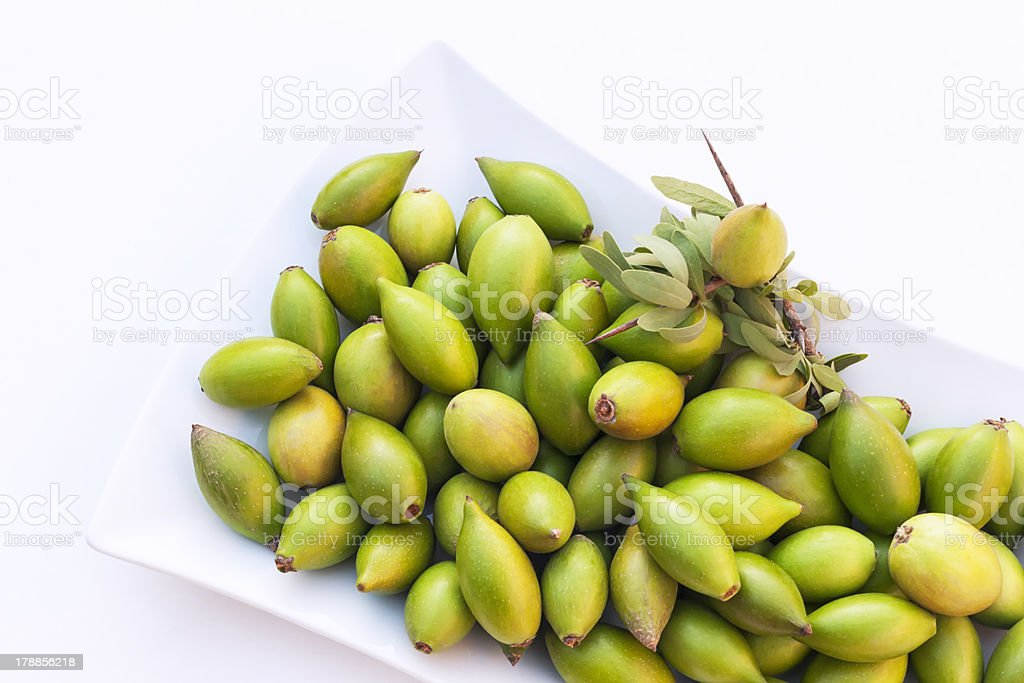 Argan nuts in a white plate. stock photo