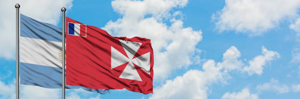 Argentina and Wallis And Futuna flag waving in the wind against white cloudy blue sky together. Diplomacy concept, international relations. stock photo