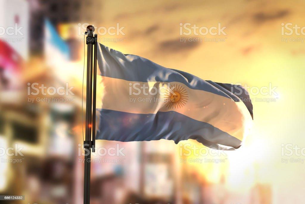 Argentina Flag Against City Blurred Background At Sunrise Backlight stock photo