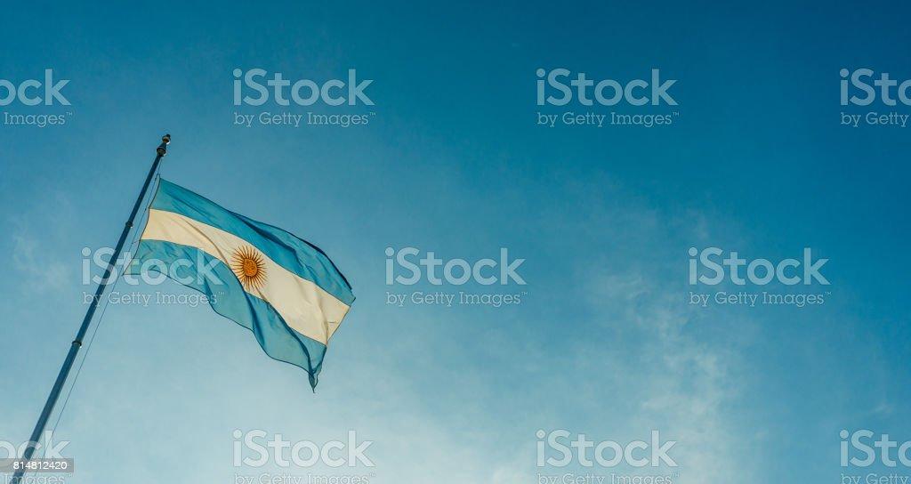 Argentinien-Fahnenschwingen gegen blauen Himmel an einem sonnigen Tag – Foto