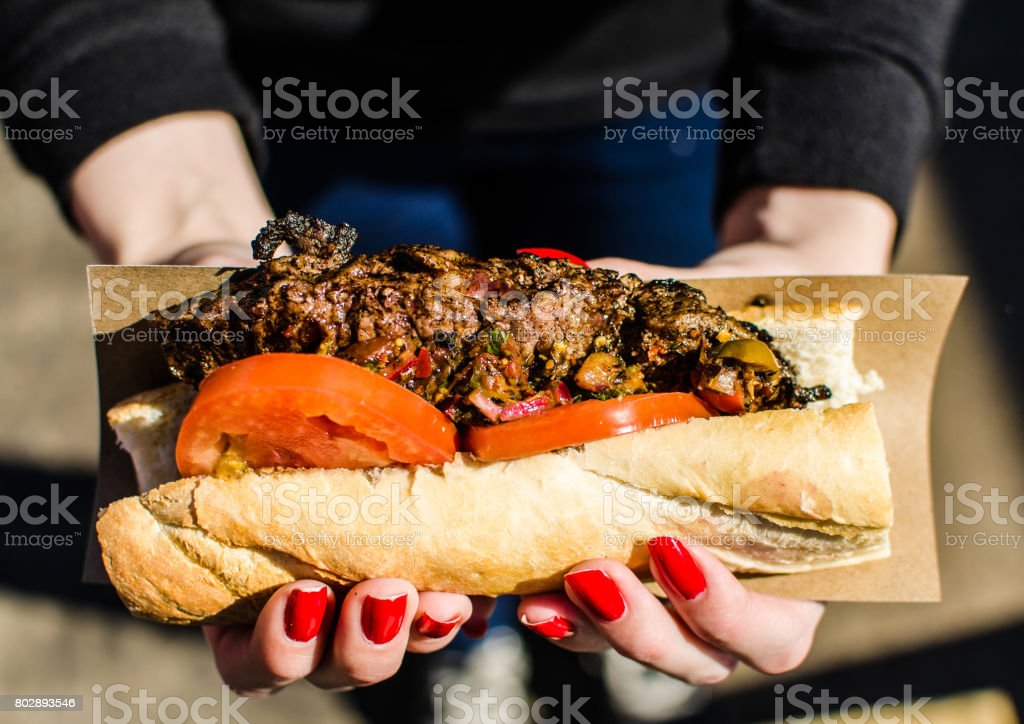 Argentina street food, traditional sandwich with New York strip steak and chimichurri sauce at a street food market stock photo
