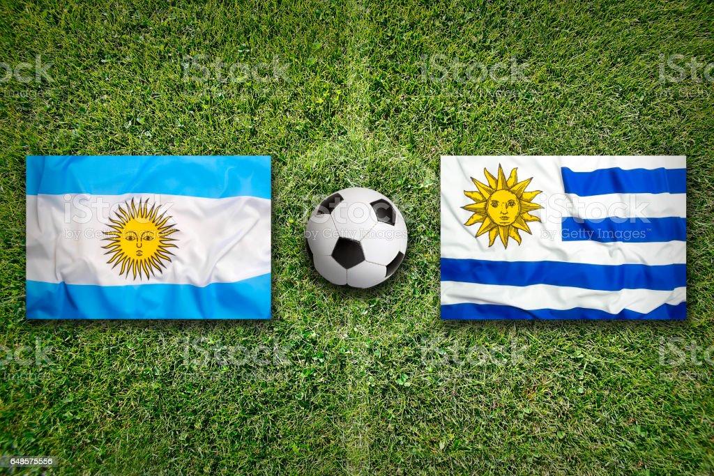 Banderas de Argentina vs Uruguay en cancha de fútbol - foto de stock