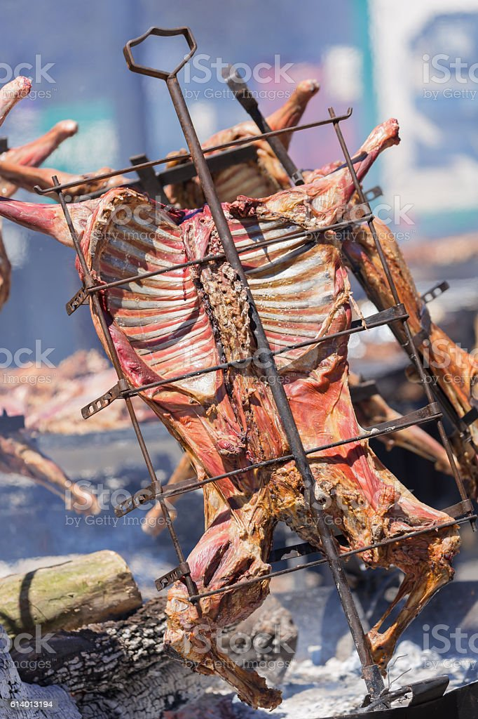 Argentine asado BBQ with entire goat on crossed grill - foto de stock