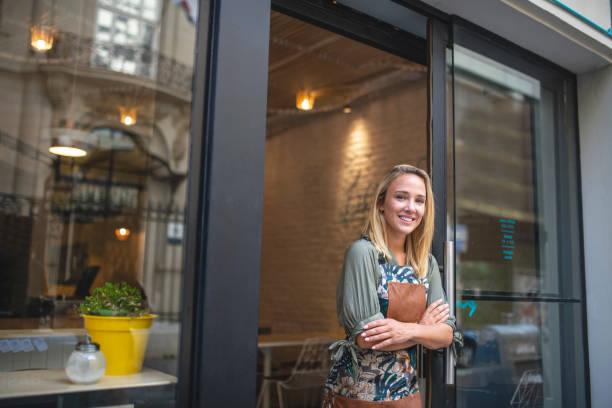 阿根廷女咖啡館老闆站在前門 - small business saturday 個照片及圖片檔