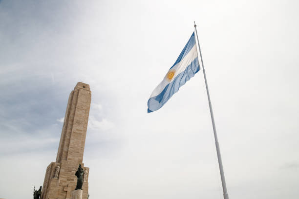 Argentine flag in front of the tower of the National Flag Monument in Rosario, Argentina stock photo
