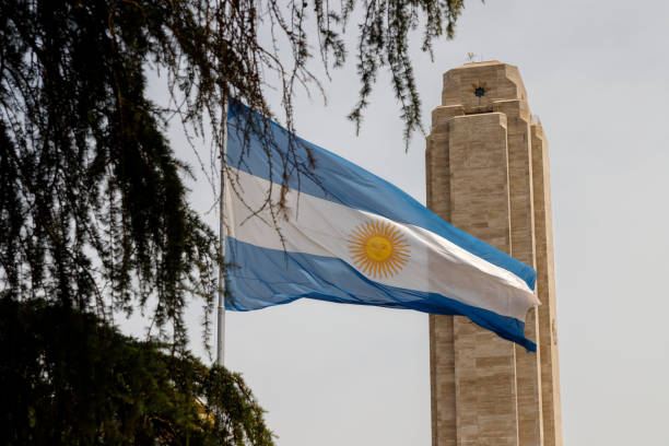 Argentine flag seen between tree branches in front of the tower of the National Flag Monument in Rosario, Argentina stock photo