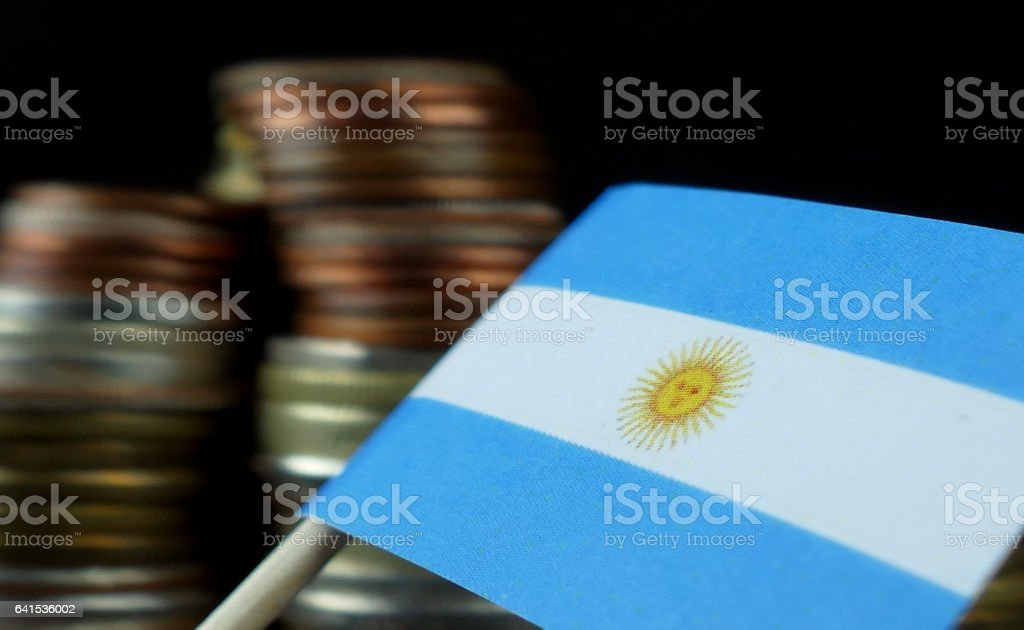 Argentine flag waving with stack of money coins macro stock photo