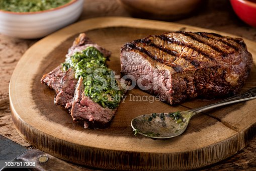 A delicious medium rare fire grilled argentina style steak with chimichurri verde sauce.