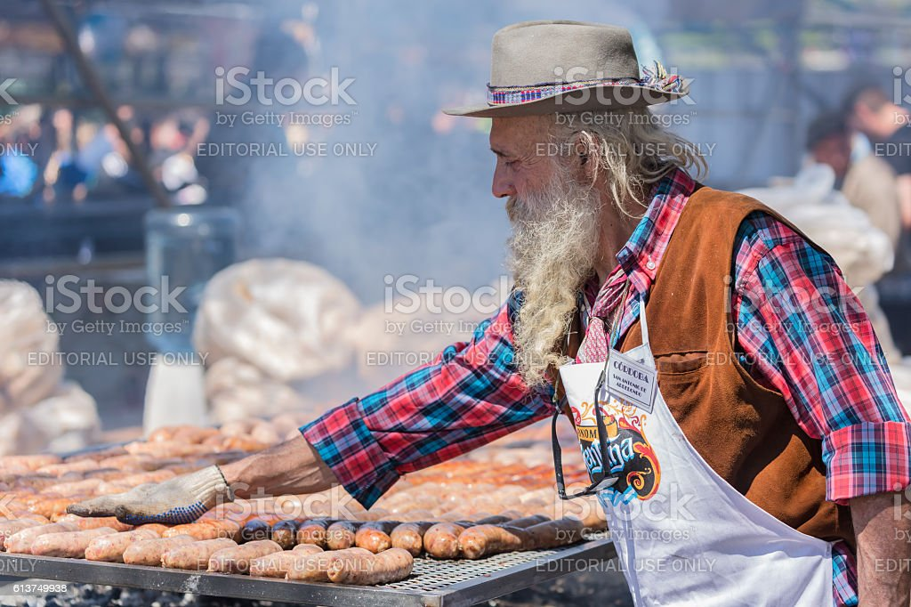Argentinean asado (BBQ) with old gaucho and sausages - foto de stock