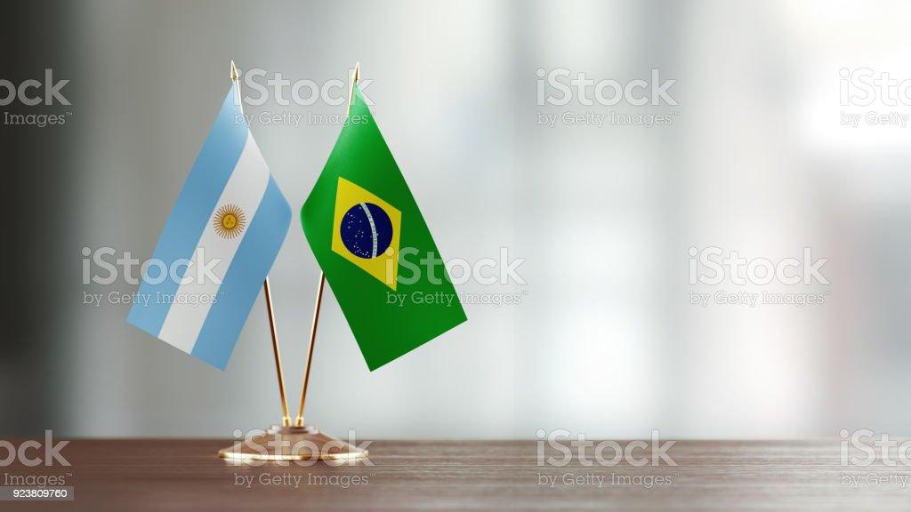 Par de la bandera Argentina y brasileña en un escritorio sobre fondo Defocused - foto de stock
