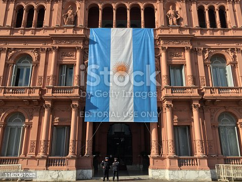 Buenos Aires, Argentina - July 14, 2019: Huge hanging argentinian flag from Casa Rosada balcony. It is there for the celebration of the independence day which is the 9th of july
