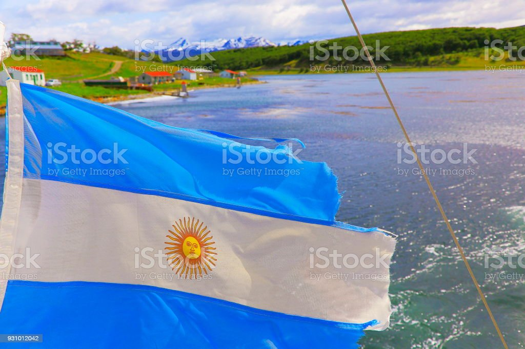 Argentinian flag winding in Beagle Channel - Andes landscape, Ushuaia - Tierra Del fuego, Argentina stock photo