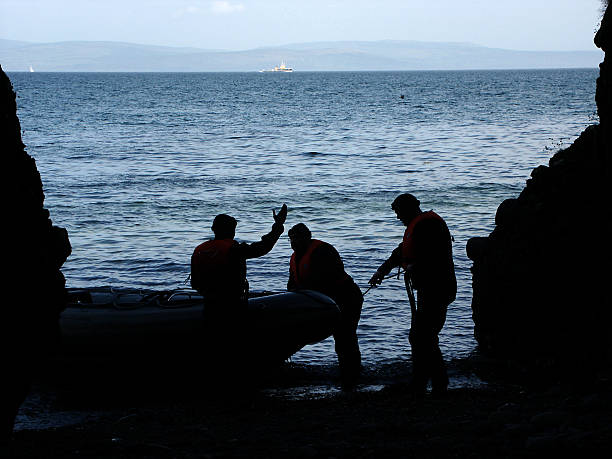 argument! Silhouette of three men arguing at the entrance to a sea cave by the Irish sea on the Scottish coast smuggling stock pictures, royalty-free photos & images