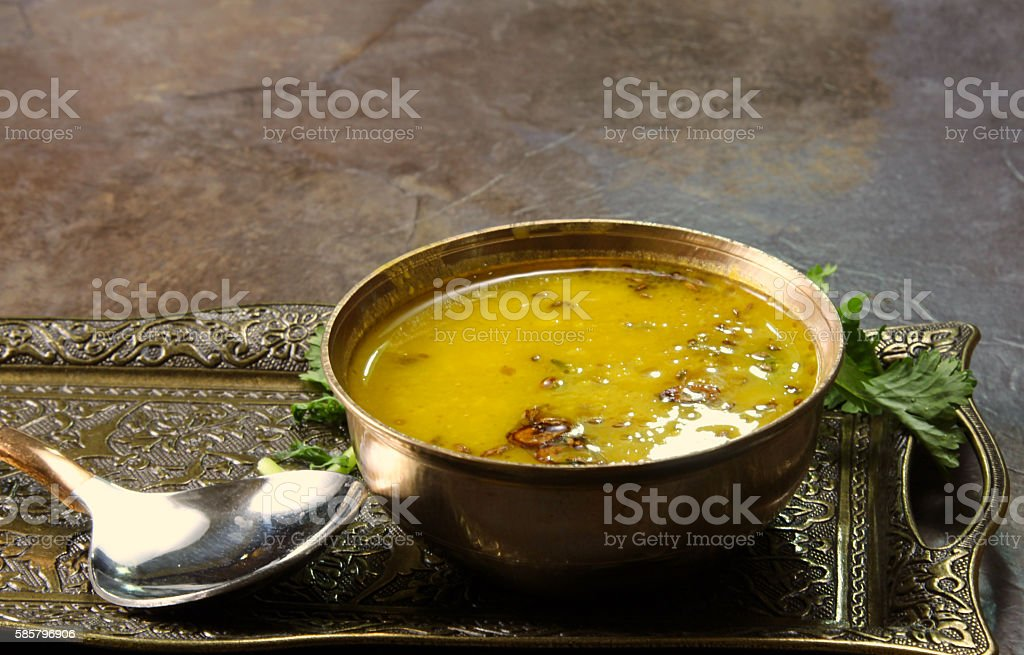 Arhar Daal Yellow Lentil soup or Arhar Daal fry with the tadka of cumin seeds, garlic and green chilies in a bowl on a tray with cilantro leaves on the side with copy space, selective focus. Cooking Stock Photo