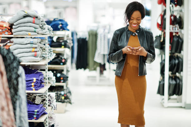 Arican american woman in clothes store stock photo
