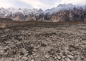 Arid climate, dry cracked drought field with Passu Cathedral mountain landscape in Pakistan