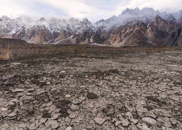Arid climate, dry cracked drought field with Passu Cathedral mountain landscape in Pakistan stock photo