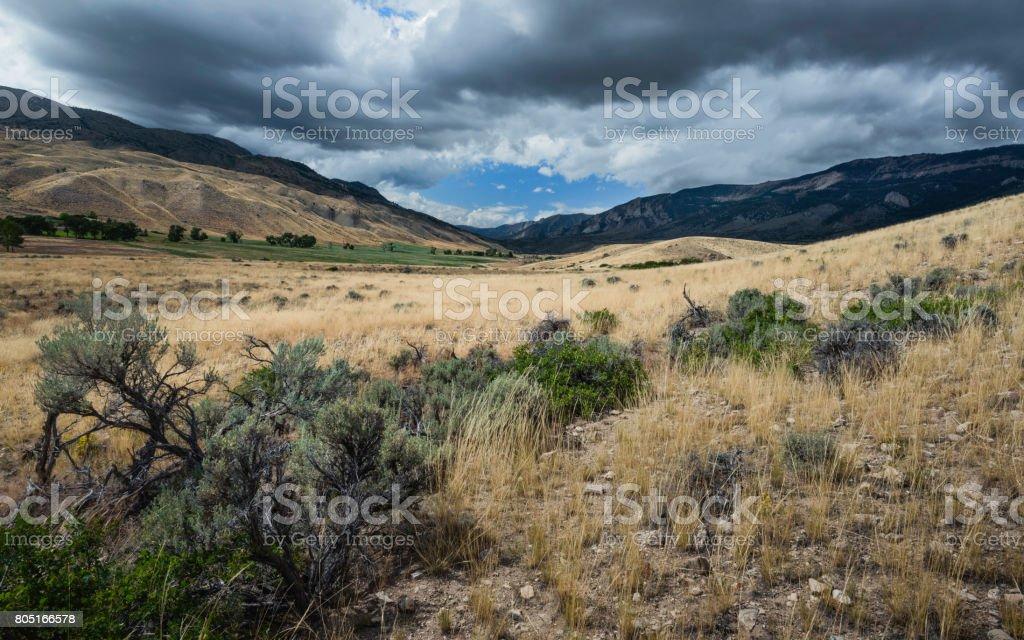 Arid prairie, sagebrush, and Rocky Mountains near Cody, Wyoming, USA. stock photo