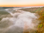 Aerial view of fog rising over river valley at sunrise.