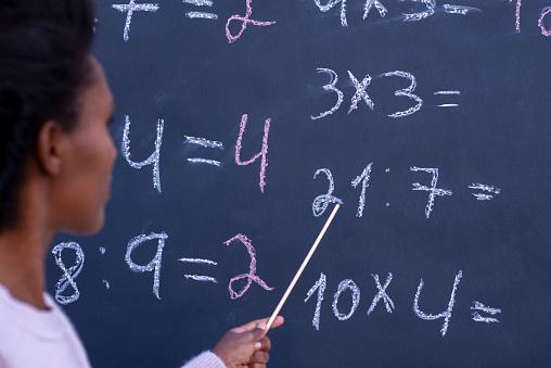 istock Arithmetic math teacher teaching division and multiplication. 1242082241