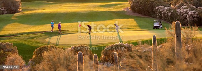 Mesa, Arizona, United States - December 6, 2014: A foursome of golfers putting out on a beautiful resort golf course in Phoenix, Arizona. Phoenix is one of the world's most popular golfing hot spots. Thousands of Canadians and people living in the northern United States flock to the region each winter. The region is known for its beautiful desert golf courses.