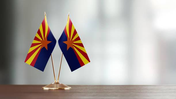 Par de bandeira do estado do Arizona em uma mesa sobre fundo desfocado - foto de acervo