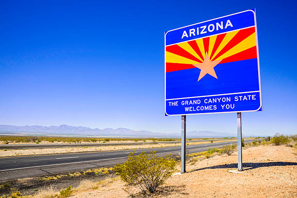 Arizona State Line Welcome Sign - highway desert, mountains, sky stock photo