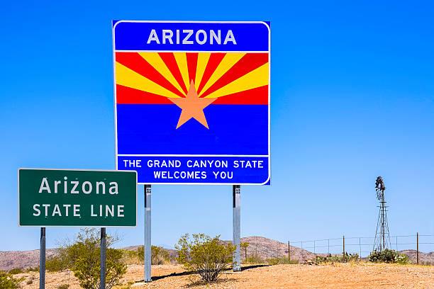 Arizona State Line Sinal de boas-vindas com moinho de vento, as montanhas e céu - foto de acervo