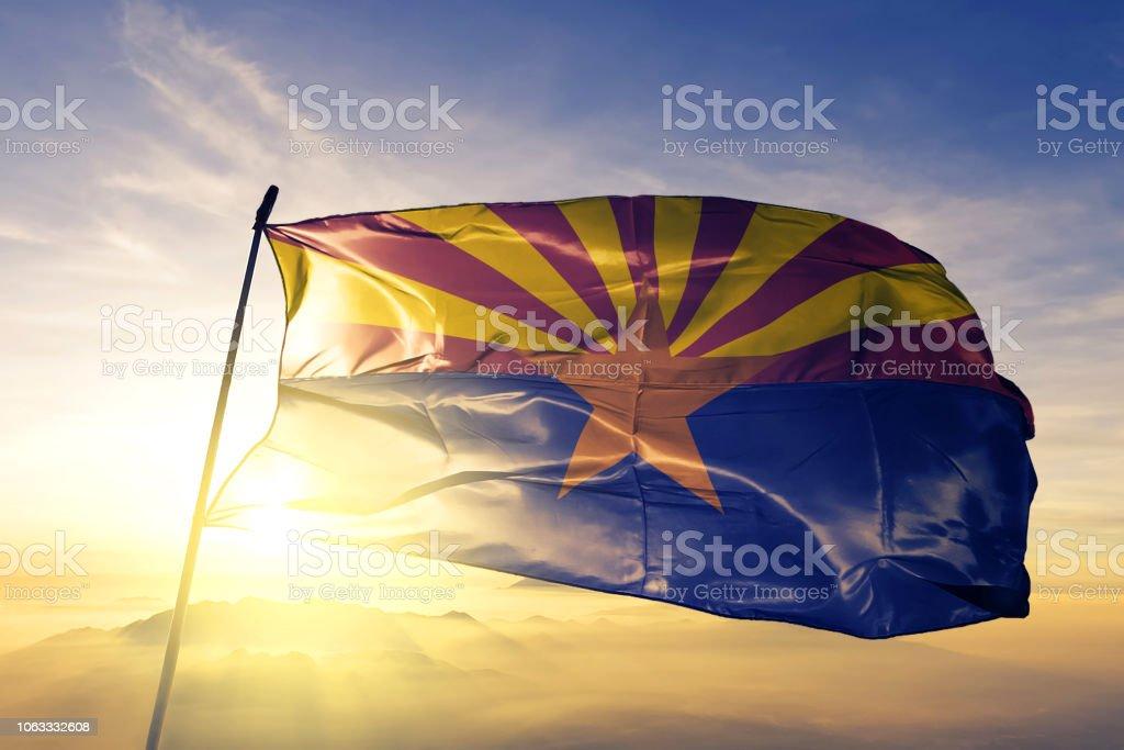 Arizona estado dos Estados Unidos bandeira pano tecido têxtil acenando do nevoeiro de névoa superior ao nascer do sol - foto de acervo