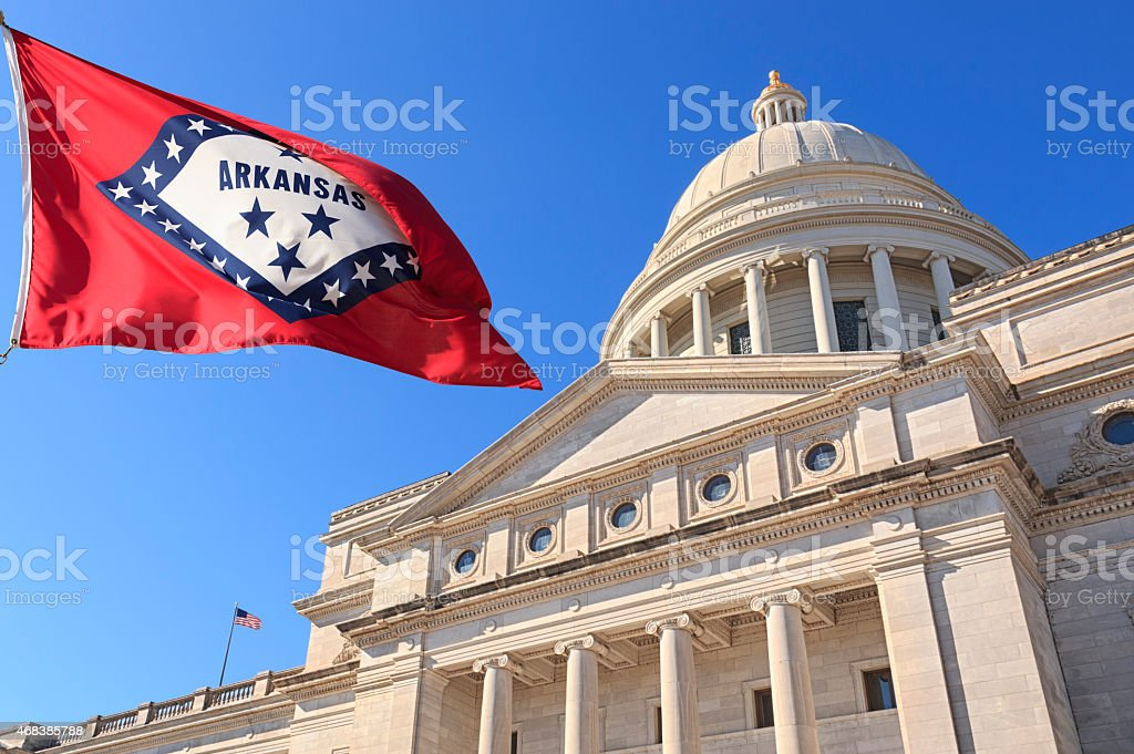 Arkansas flag flying high beside the State Capitol Building stock photo