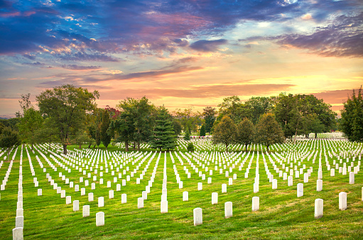 Grave stones at Arlington National Cemetery in Washington DC at sunset.