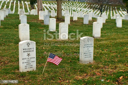 Arlington,VA, USA March 28, 2014 A small American flag waves amongst the numerous graves at Arlington National Cemetery in Virginia