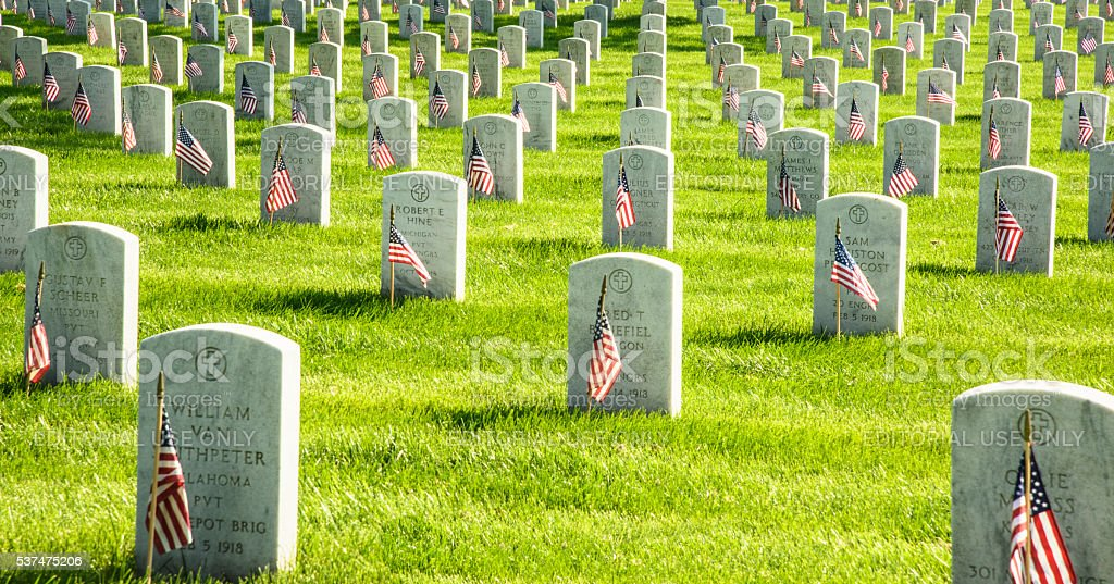 Arlington National Cemetery Arlington, Virginia, USA-May 29, 2016:Arlington National Cemetery Memorial Day Flags placed at each gravesite honoring the fallen in wars fought by Americans. The graves seem to goon forever in this image, no people present  2016 Stock Photo