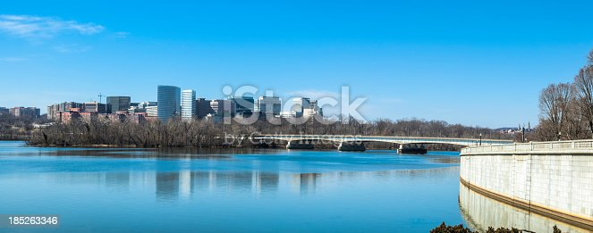 The skyline of Arlington, Virginia, looking north on the Potomac River under a brilliant blue sky.  The skyscrapers cast their reflection on the glassy calm waters of the river.  Many of the skyscrapers are defense industry buildings.