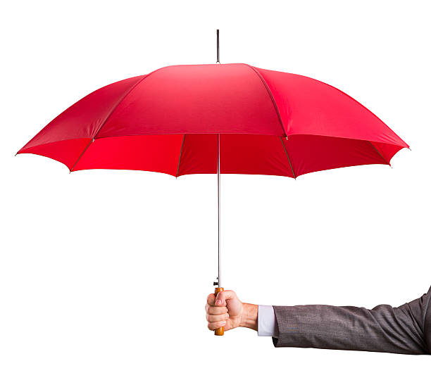 Arm in suit sleeve holding out a red umbrella stock photo
