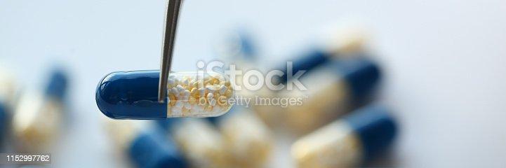 1092248526istockphoto Arm lifting up pill with tweezers closeup 1152997762