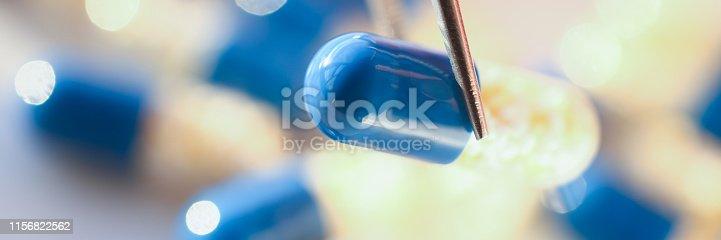 1092248526istockphoto Arm lifting up pill with tweezers closeup 1156822562
