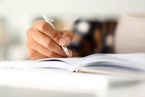 ramię czarnej kobiety napisać historię w notatniku - notes zdjęcia i obrazy z banku zdjęć
