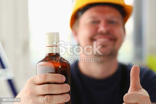 1073474208 istock photo Arm of drunken worker in yellow helmet 882350414