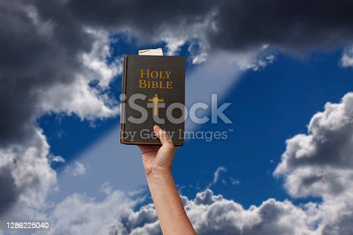 istock Arm raised into the air with hand reaching up and holding the Holy Bible. Dark blue sky and a ray of light coming through dramatic blurred clouds. 1286225040
