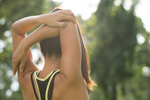 Arm stretch Rear view of woman stretching her arm and shoulder bicep stock pictures, royalty-free photos & images