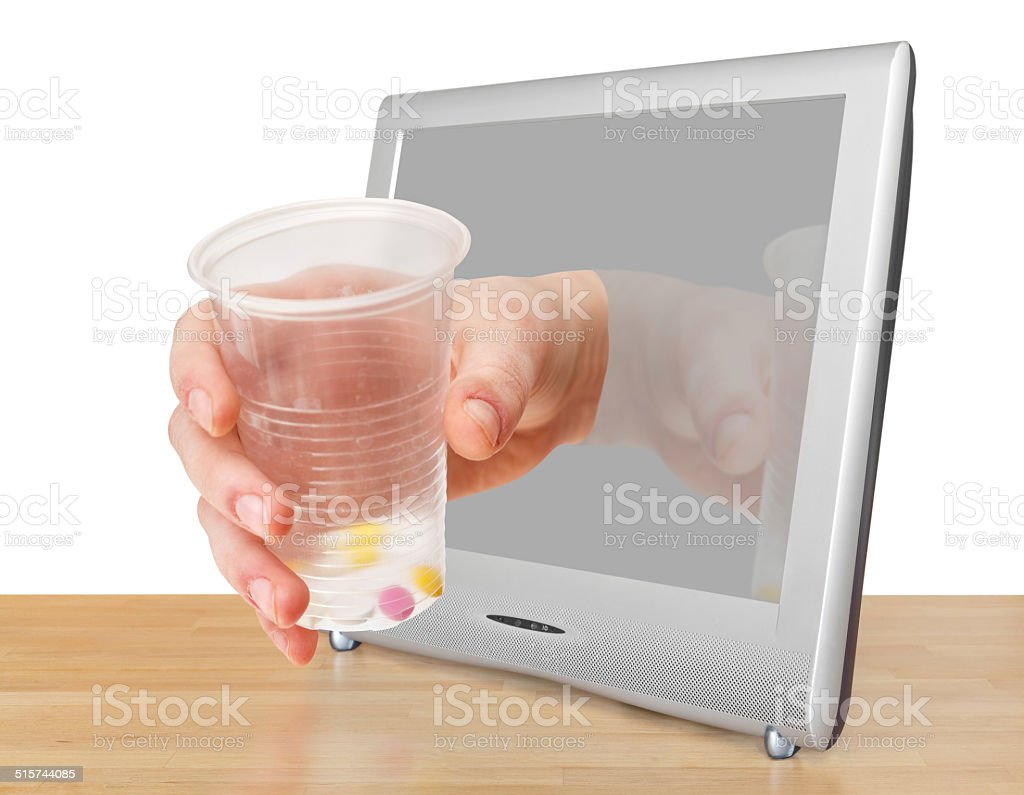 arm with glass with pills leans out TV screen stock photo